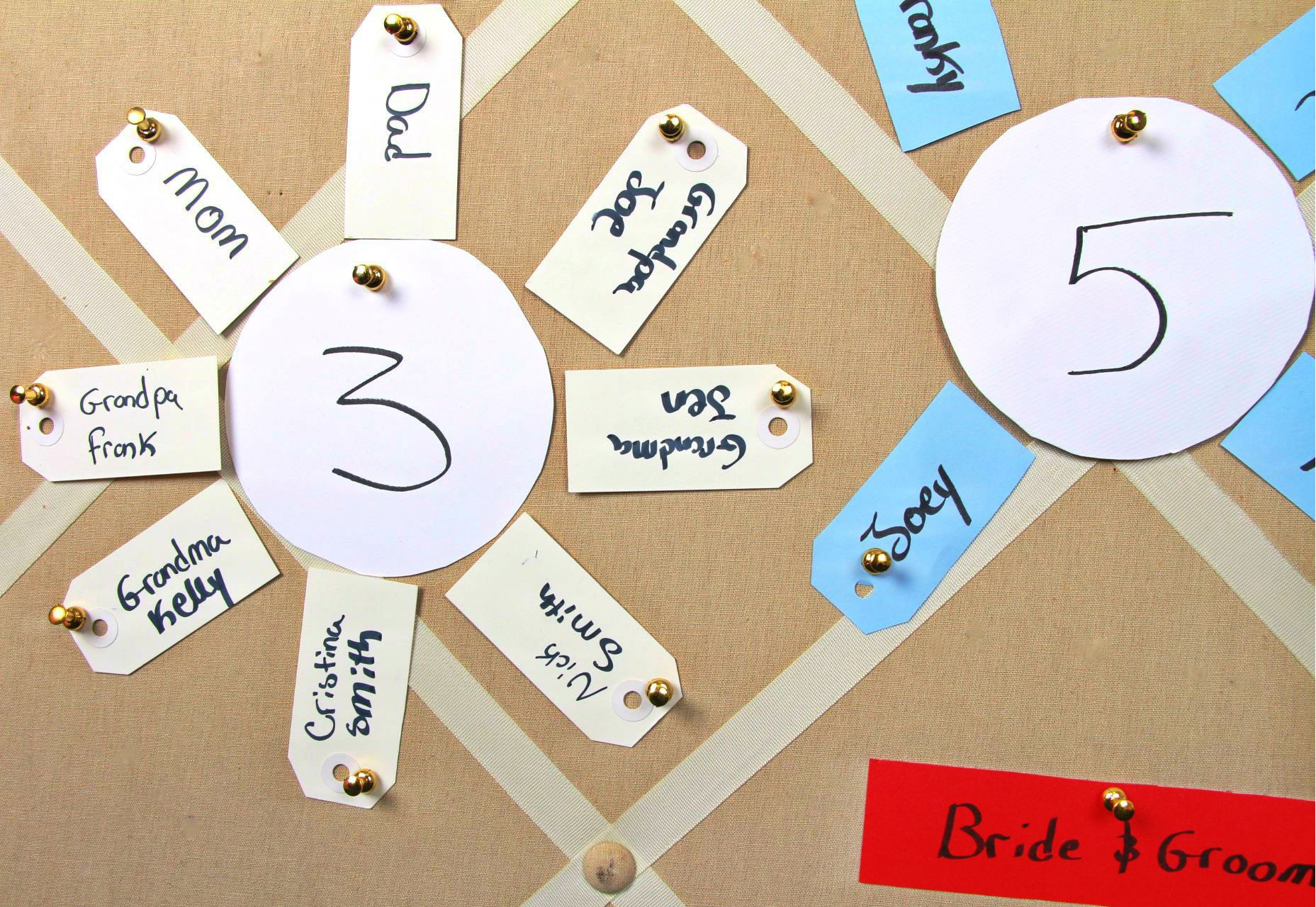 how to make a wedding seating chart with paper, push pins, and gift tags