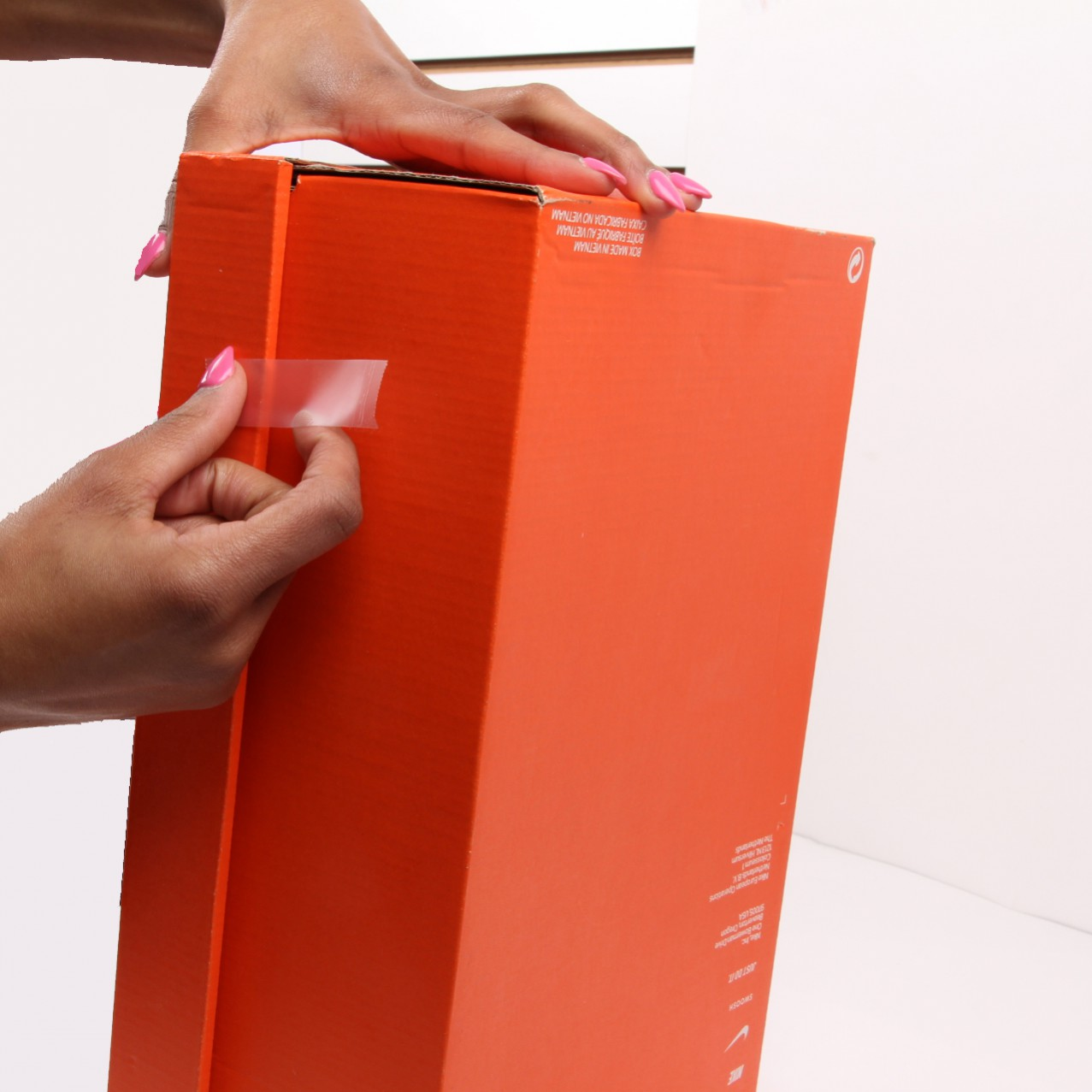 hands taping sides of nike shoe box to use as birdhouse