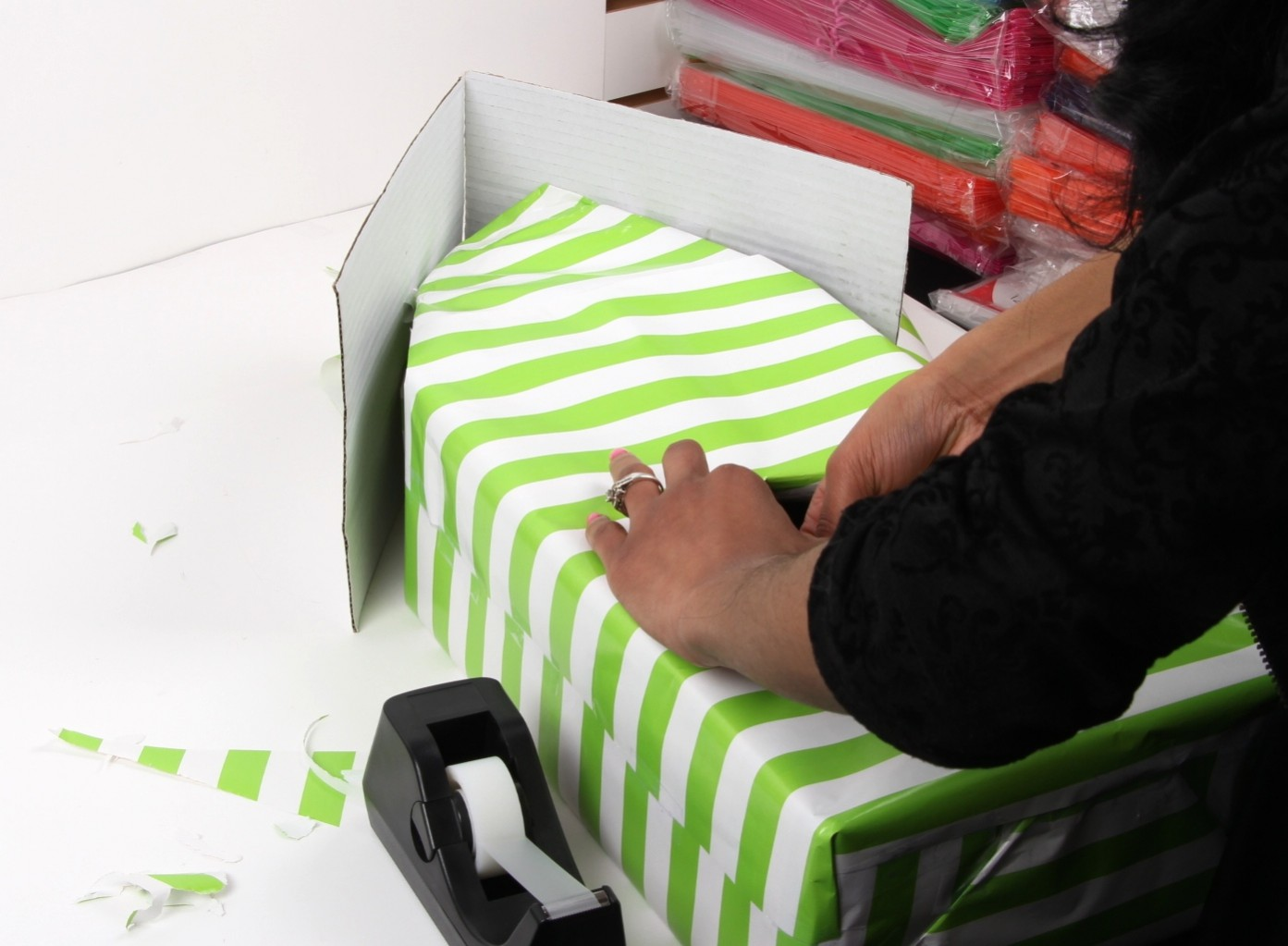 woman covering shoebox in wrapping paper