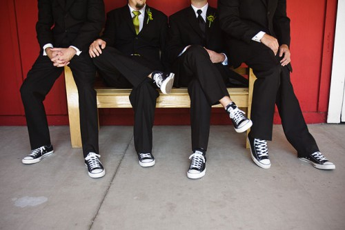 groomsmen sitting on bench with black and white matching converses