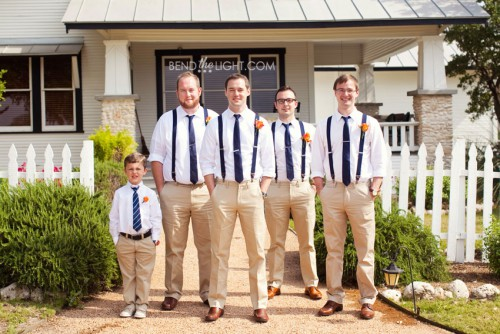 row of men in khaki pants and navy blue suspenders in front of house