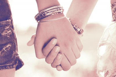 two women holding hands with bracelets