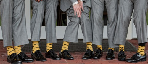 row of gray dress pants with black dress shoes and yellow mustache socks