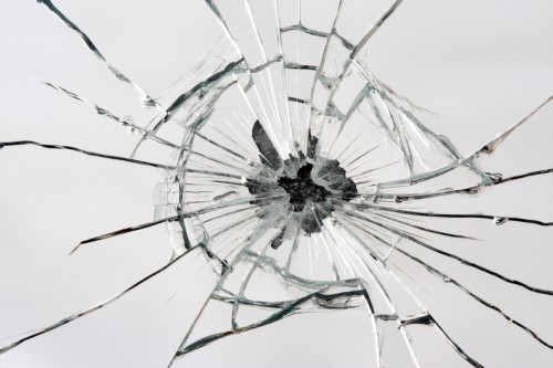 broken glass with cracks rippling from black hole