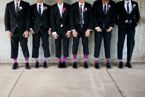 row of groomsmen in black and white tuxes lifting pants to show matching purple socks