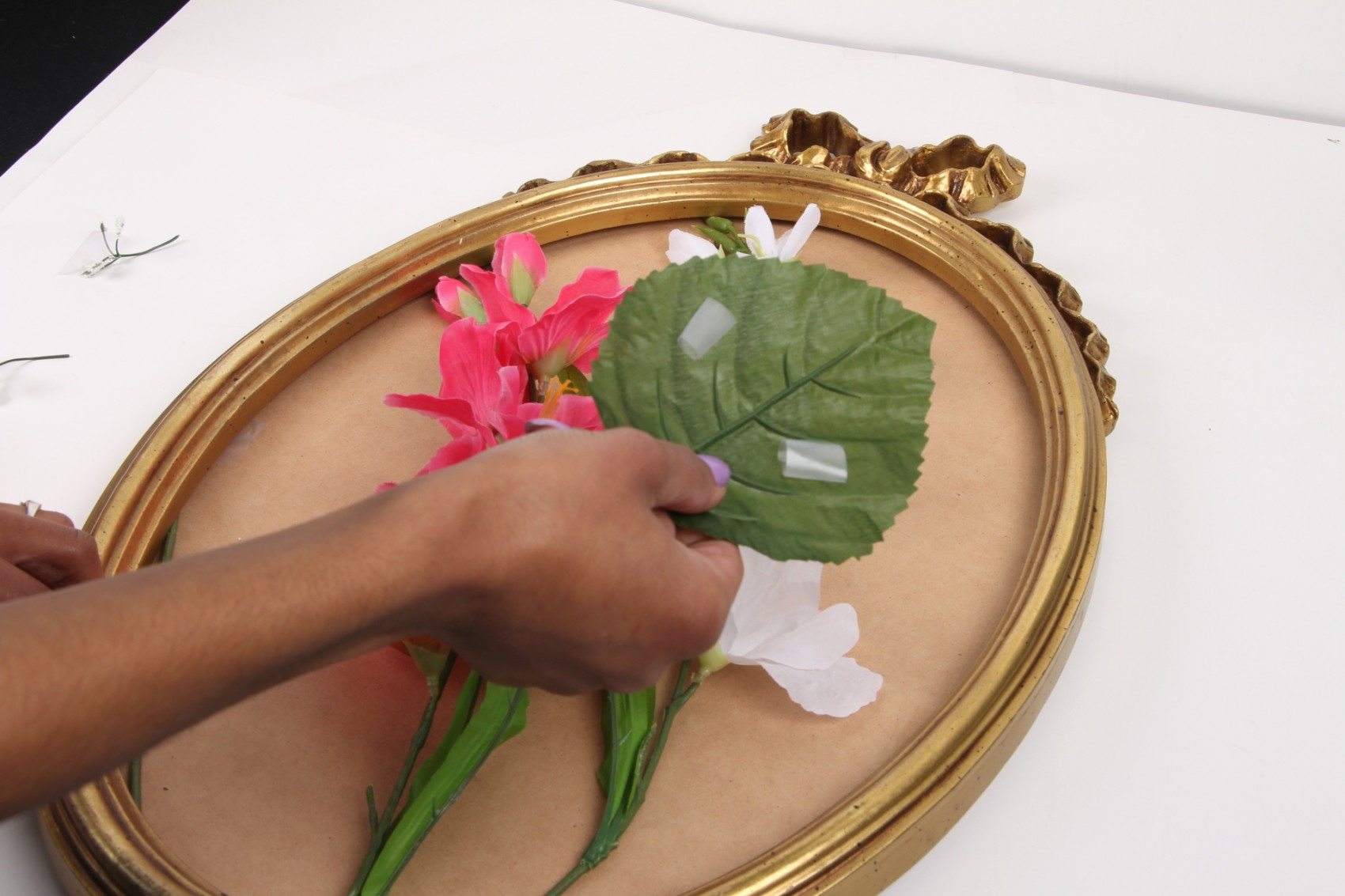 hands taping pink and white silk flowers and leaves to mirror base