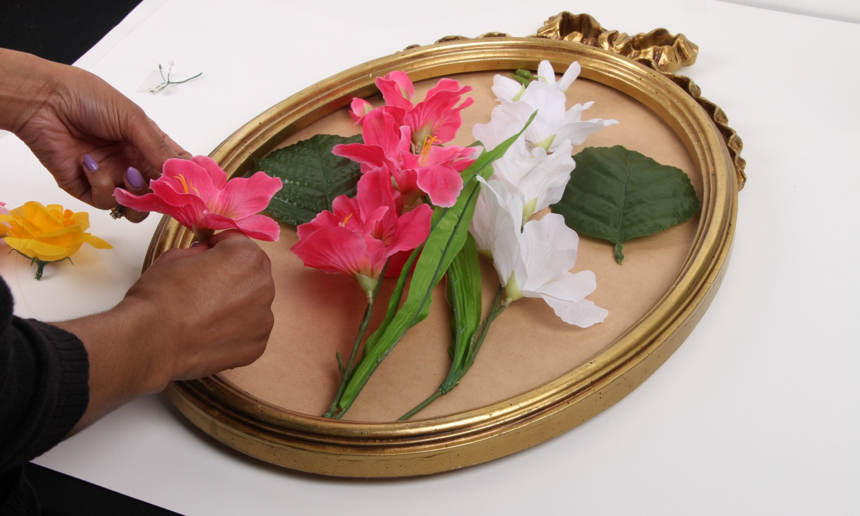 hands taping and attaching fake flowers to broken mirror
