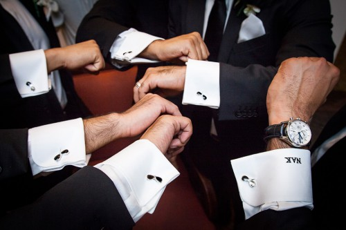 men in black and white tuxes holding out matching sunglasses cufflinks