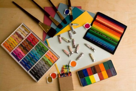 paint, oil pastels, colored pencils, crayons, colored paper, and other art materials spread out