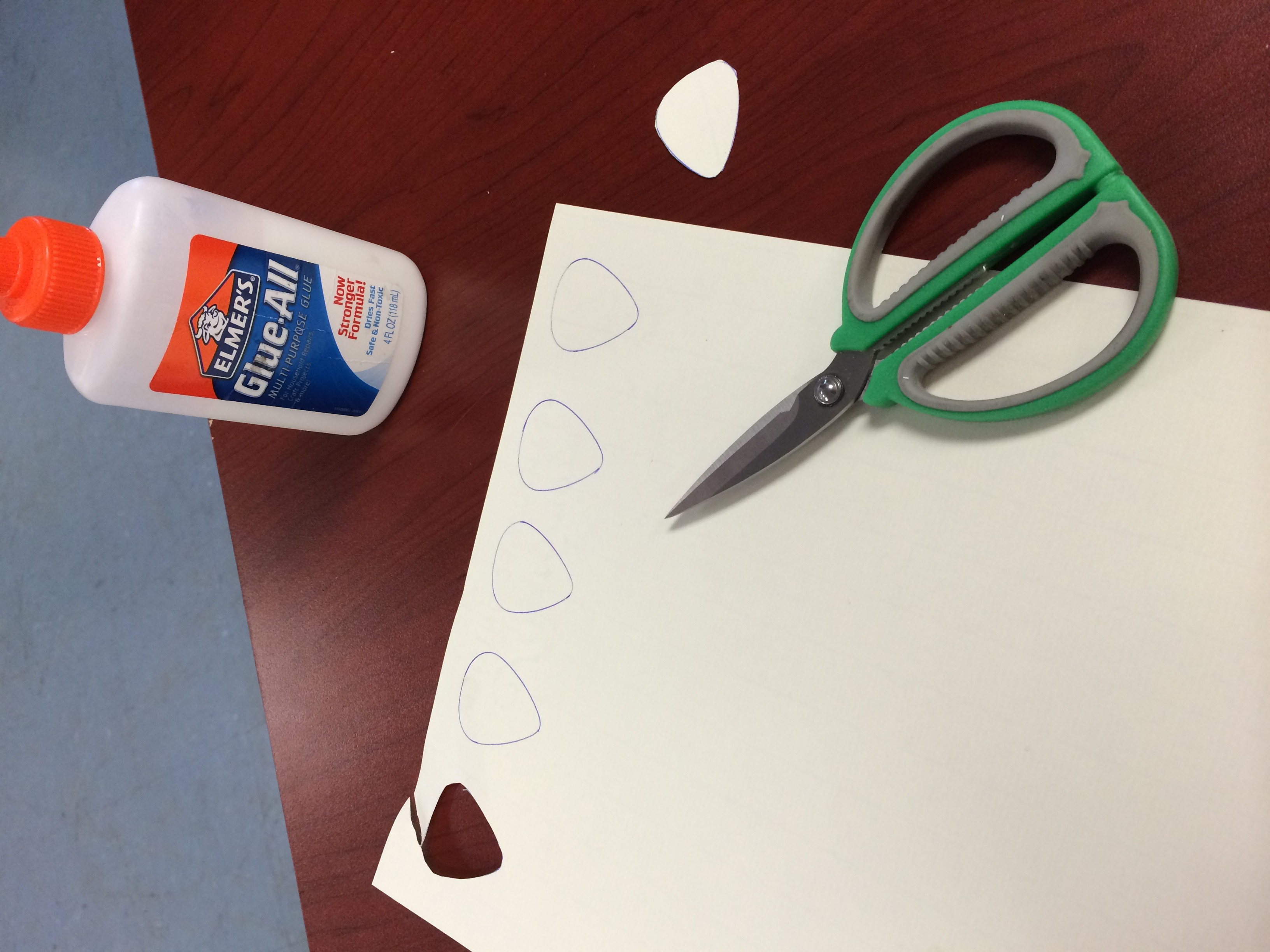 sheet of white cardstock with traced outlines of guitar picks on a desk with scissors and glue