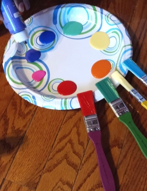 paint drops on paper plate, brushes