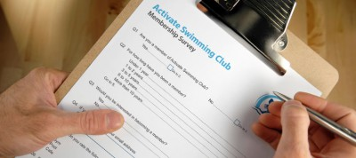 hands holding pen and membership survey