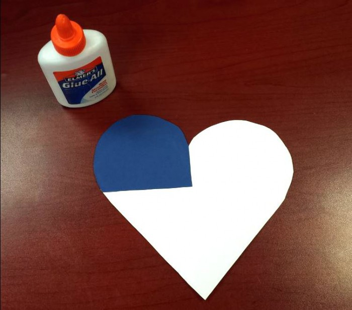 white paper heart on desk with blue paper in corner and glue bottle