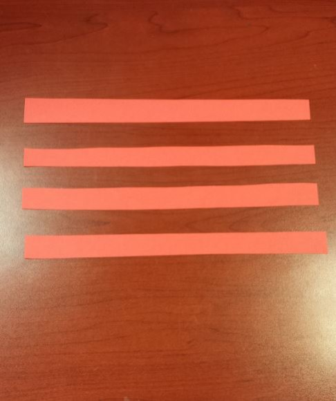 4 red paper stripes strips laid out on desk