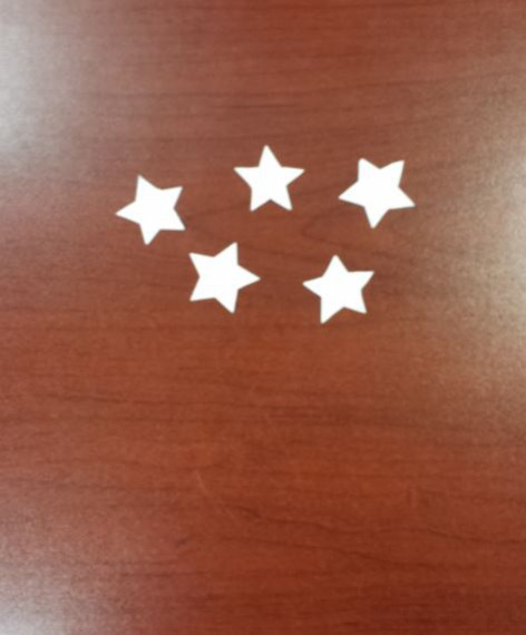 5 white paper stars cutout on wooden desk for labor day paper craft
