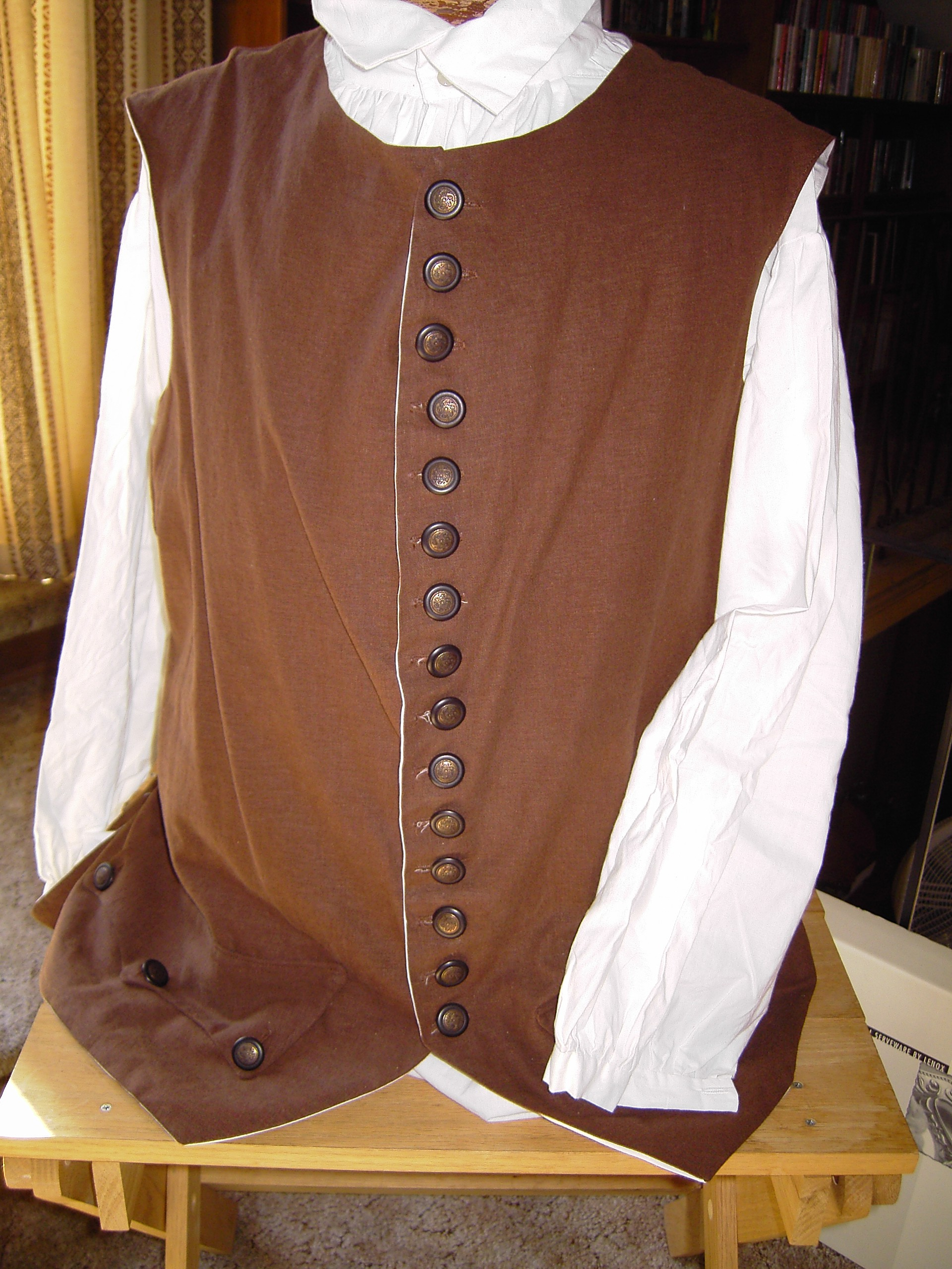 brown vest with row of brown buttons on mannequin with white long sleeve shirt