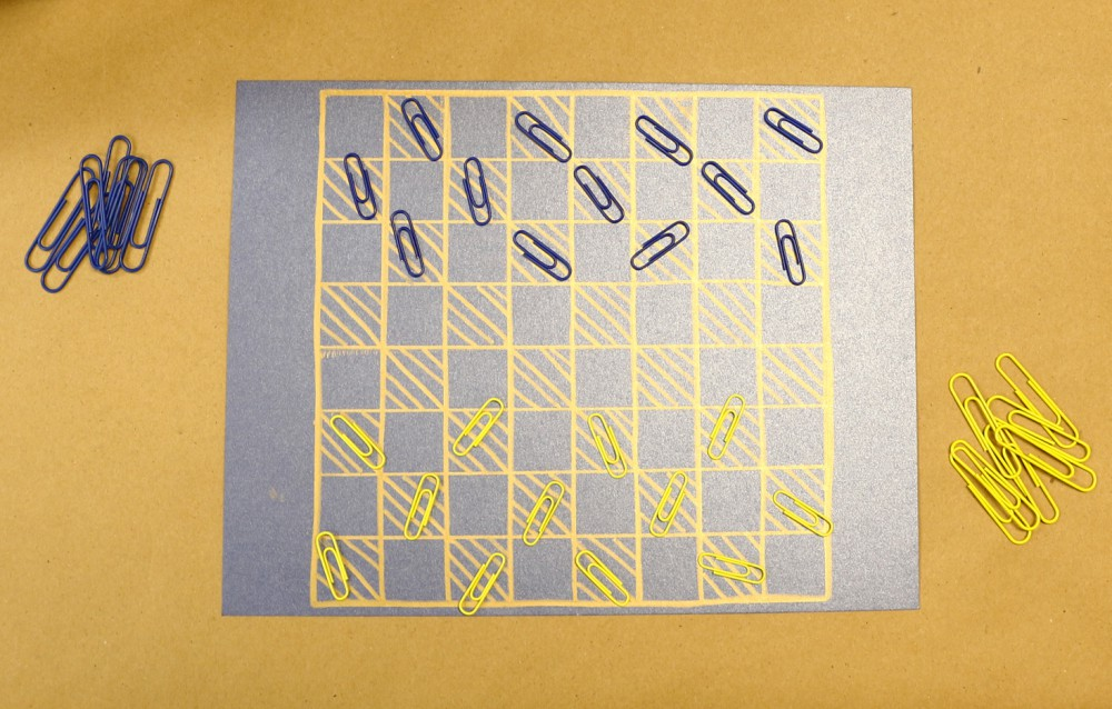 Blue and yellow paper clips as checkers