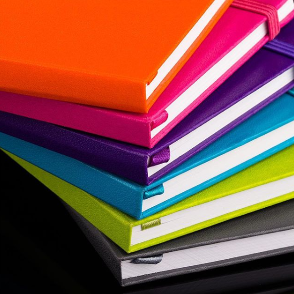 Stack of different colored journals on a dark black surface