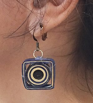 closeup of ear with circle inside square paper earring