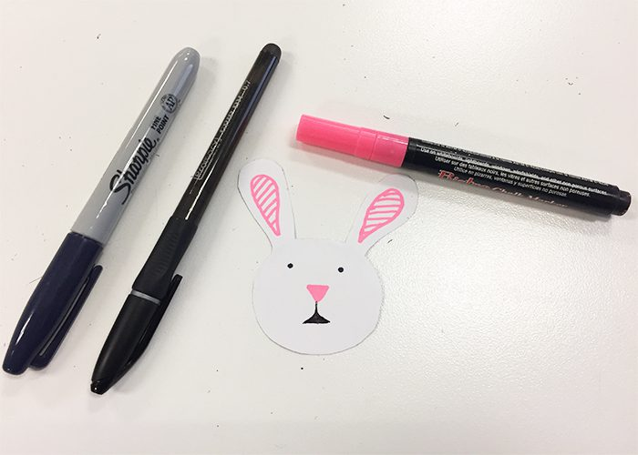Easy DIY Easter Sticker Egg Decorations, Bunny face drawn on cutout with black and pink pens and a black marker
