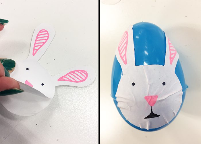 Bunny face label peeled off and stuck onto blue plastic Easter egg