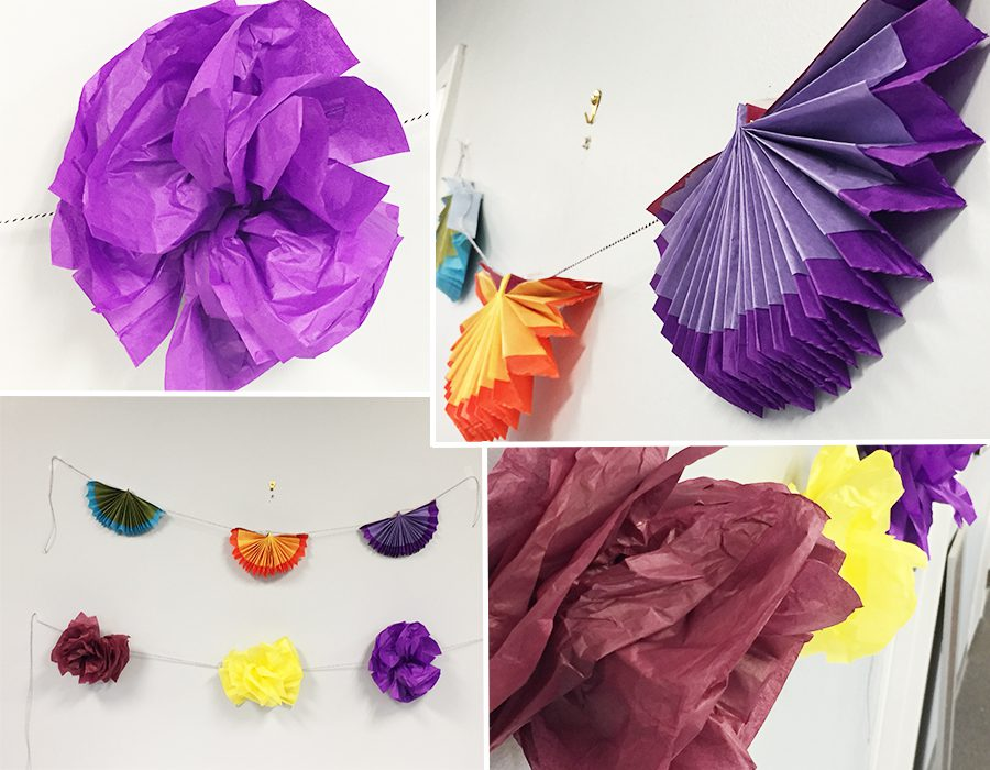 Pompom flowers and paper fans hung from wall