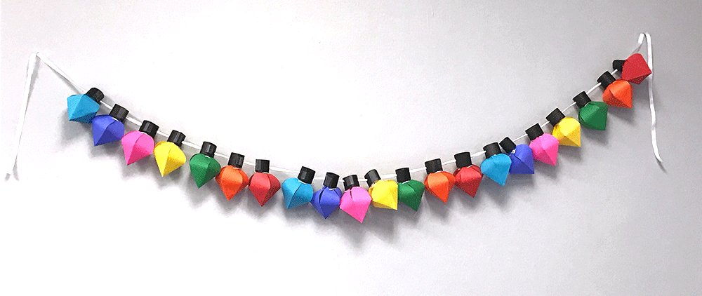String of multi-colored card DIY card stock Christmas lights hung on white wall