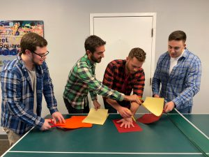 Four guys standing and chatting around orange construction on a table