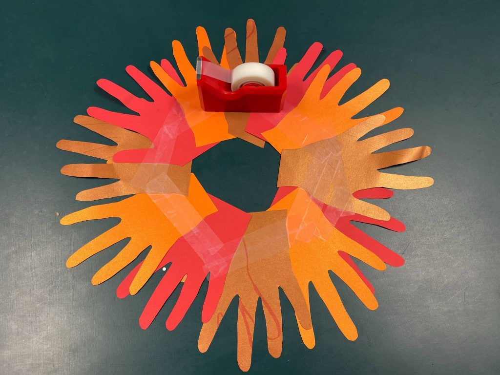 Fall-colored hand cutouts taped together in a circle with the fingers fanning out