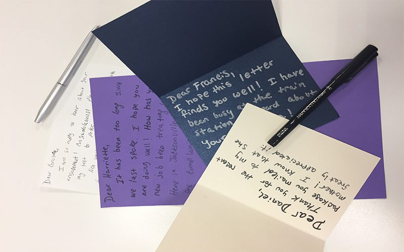 Hand-written letters on assorted colored note cards along with pens