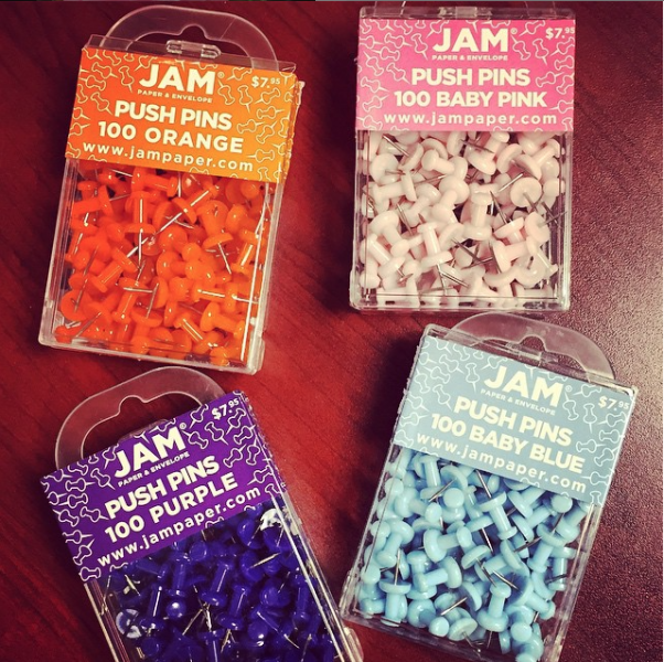boxes of jam colorful push pins in orange baby pink purple and baby blue