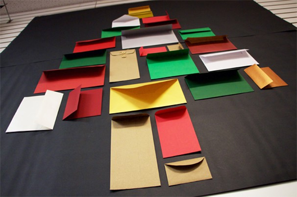 assortment of different-sized colorful envelopes in shape of christmas tree advent calendar idea