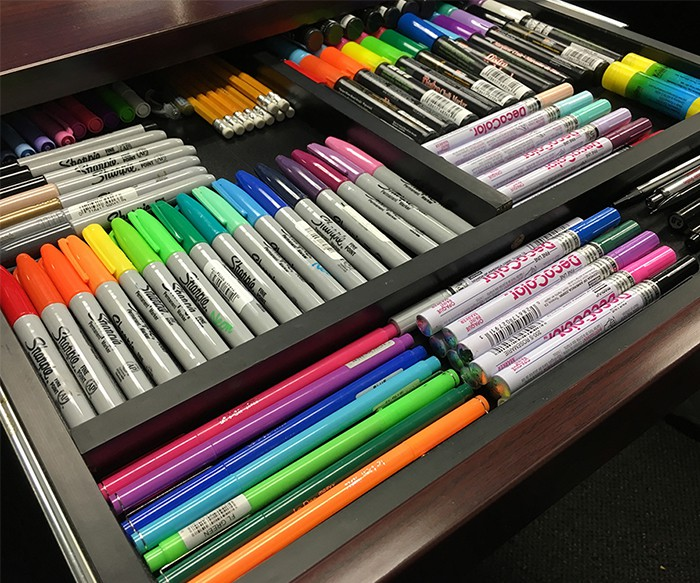 colored markers pens and pencils color-coordinated in drawer