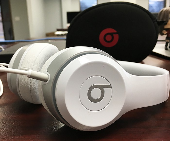 white and silver beats headphones with black and red beats headphone case on desk