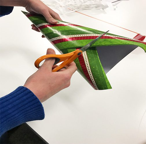 Cutting excess wrapping paper from cone with scissors
