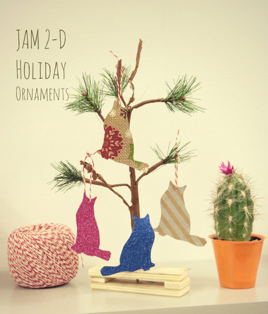 Small tree with paper cutout cats hung from it, along with twine and a small cactus