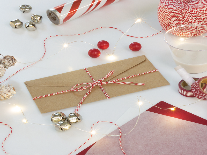 Small jingle bells, red decorative paper, red and white craft string, and gift wrap all surrounding a brown Kraft envelope with candy cane ribbon