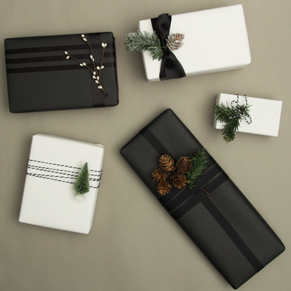 holiday wrapping trend 1: 5 black and white wrapped presents with pine cone decorations.
