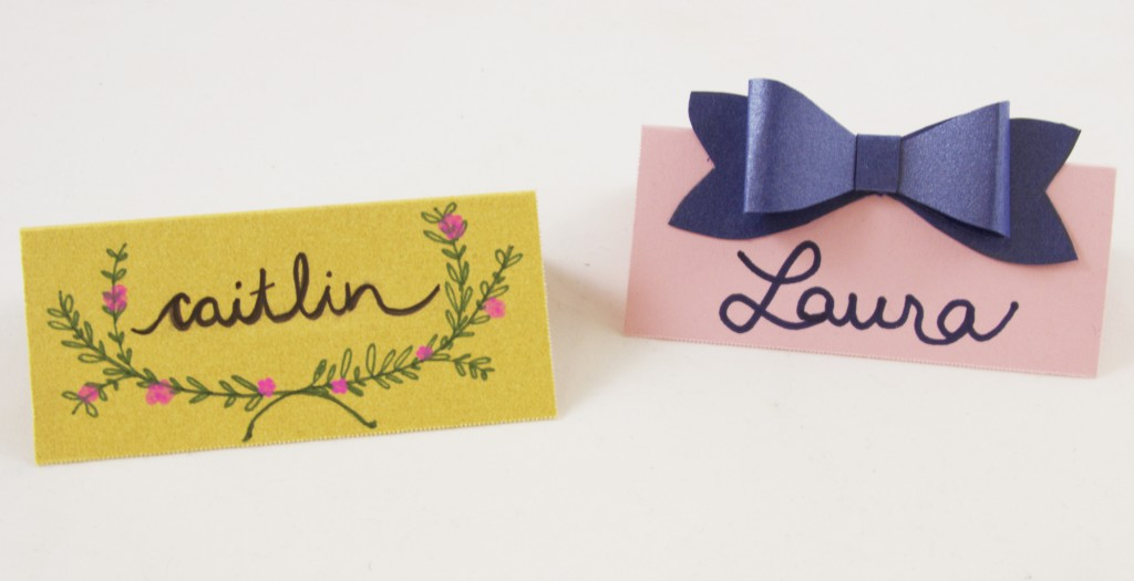 Two light-colored place cards with dainty decorations.