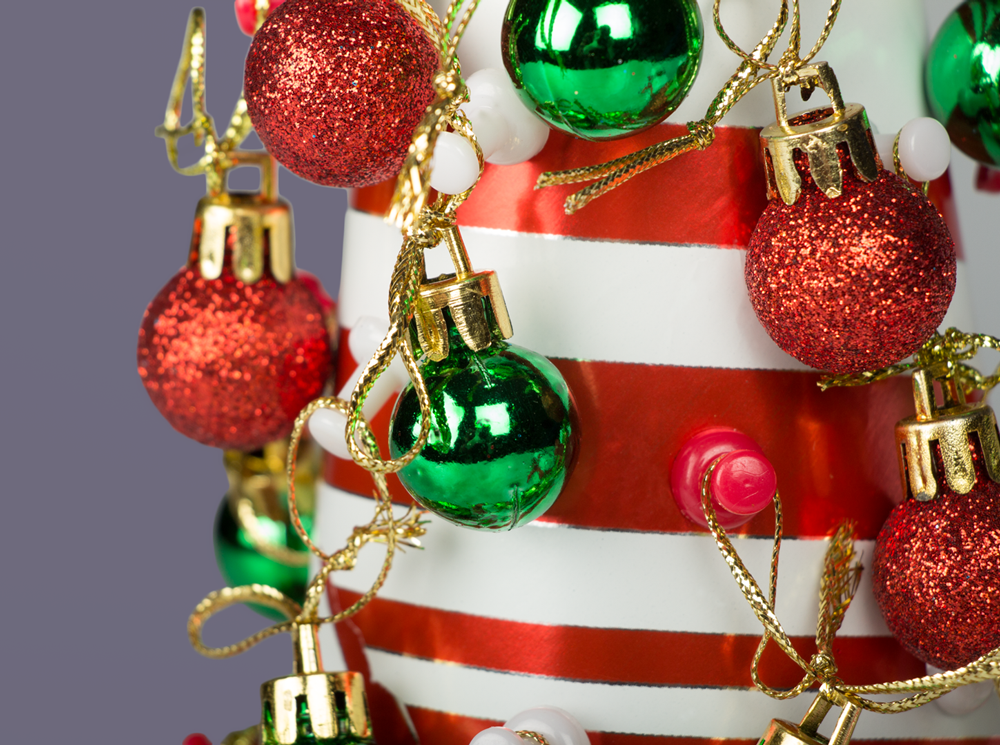 red and white striped tabletop christmas tree with green and red ornaments and pushpins