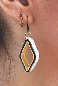 closeup of ear with large open square paper earrings