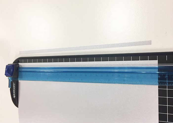 black paper and blue paper cutter with white paper