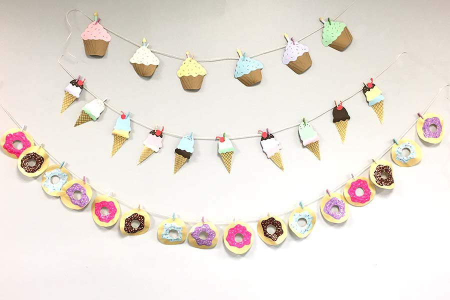 cupcake ice cream and donut dessert garland banners against white wall background