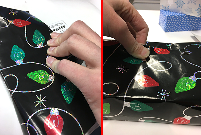 Hands wrapping a gift in black decorative wrap, pulling the paper tight over the gift
