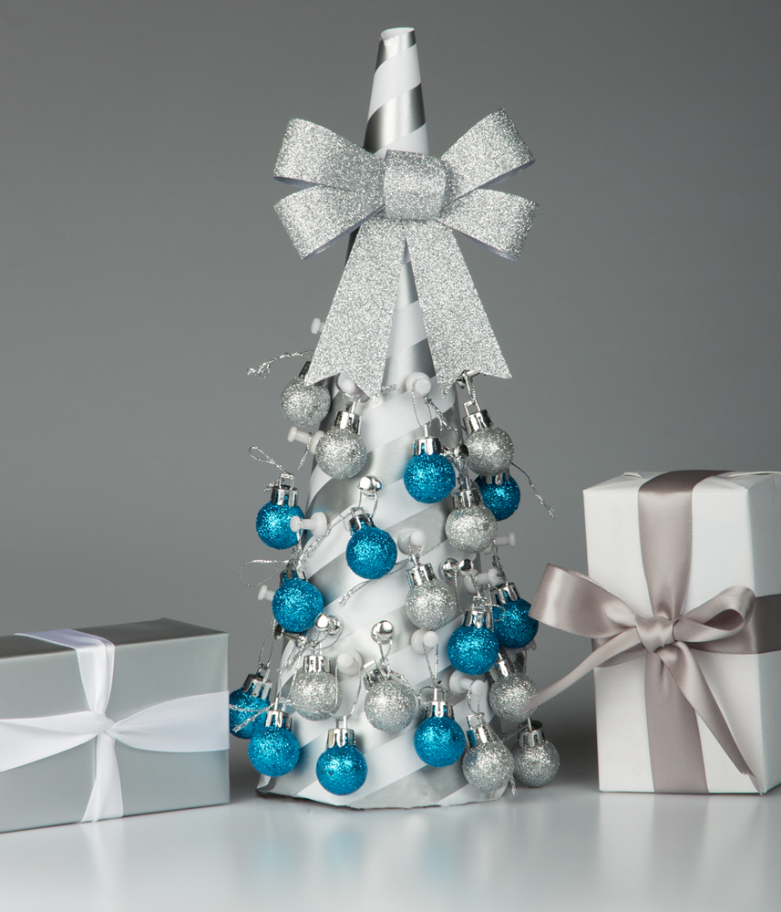 silver and blue themed tabletop christmas tree with silver wrapped gift boxes