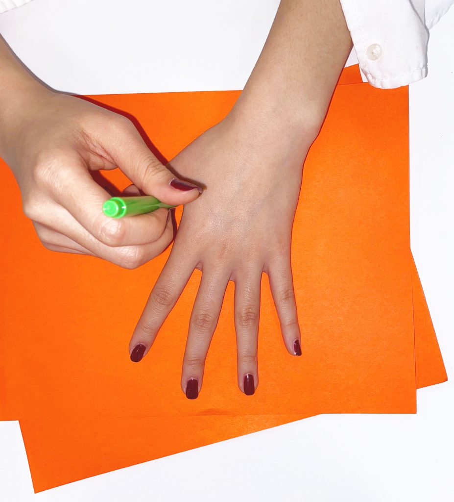 A girl using a green pen to trace her hand on orange construction paper