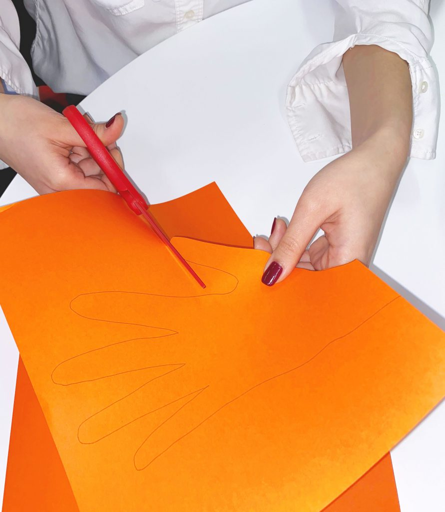 Girl using green scissors to cut out an orange tracing of her hand
