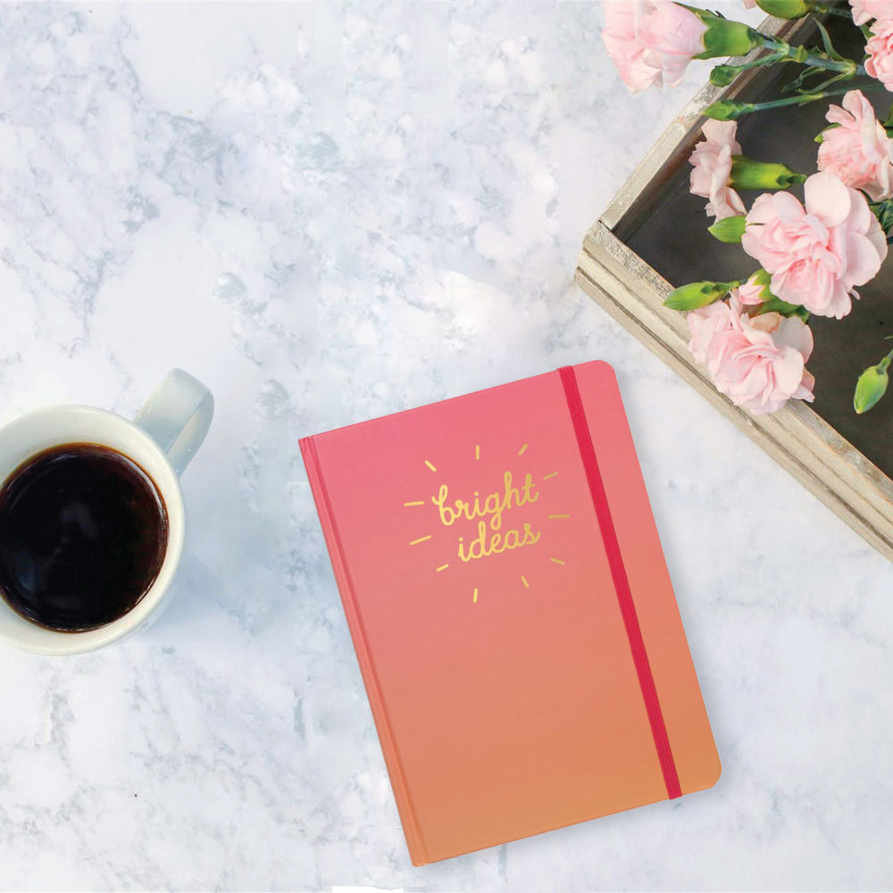 "Cup of coffee, a pink journal titled ""Bright Ideas"" and pink roses on a white granite counter"