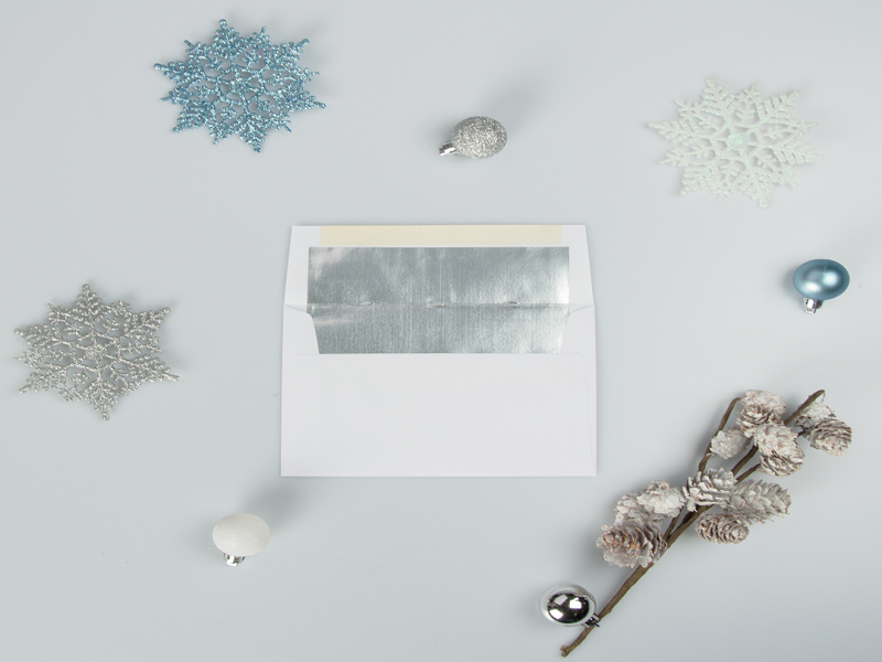 White envelope, small jingle bells, blue and silver decorative snowflakes