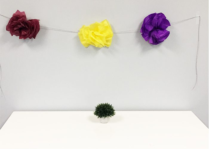 Yellow, burgundy, and purple pompom flowers strung from wall with twine